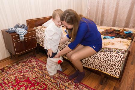 niños vistiendose: Mamá pone a su hijo en ropa de lujo listos para las vacaciones Foto de archivo
