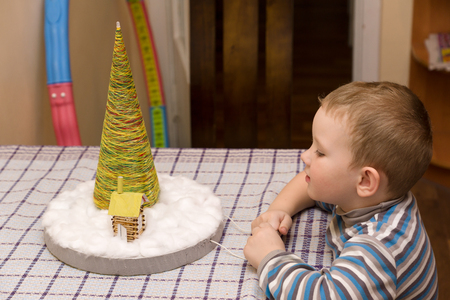 sees: little boy sitting at the table and sees a homemade Christmas tree