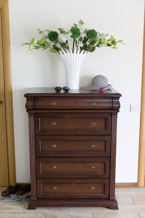 dresser: the dresser from a brown tree on which is cost by flowers Stock Photo