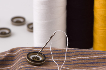 sewing cotton: we sew buttons a sharp needle with a thread Stock Photo