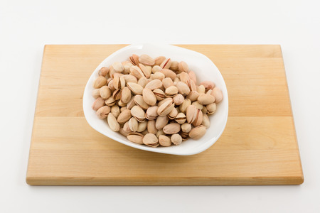 plateful: the plateful of pistachios costs on a plate on a white background