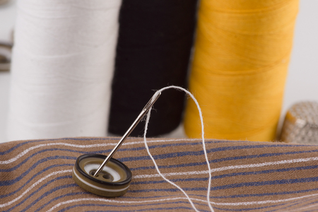 thread: we sew buttons a sharp needle with a thread Stock Photo