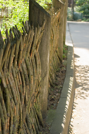 the wattle fence is made of fresh branches and guards the house from the road