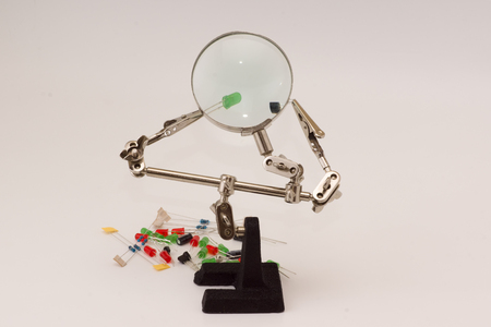 electrolytic: set of radio-electronic details of different color under magnifying glass
