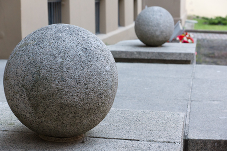gravitational: two big granite full-spheres are located at an input to the building