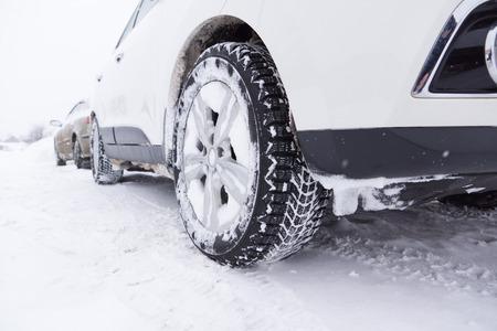 auto's met winterbanden op de met sneeuw bedekte grond