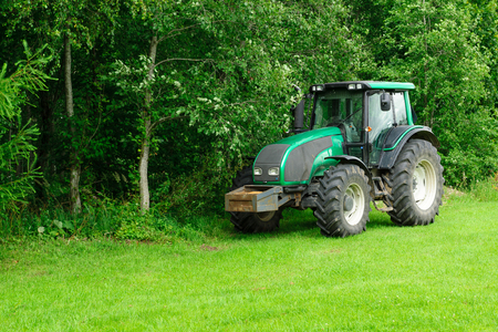 iowa agriculture: the green tractor stopped in the field of near wood