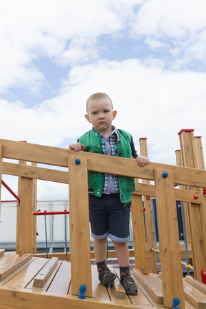 3 4 years: the little serious boy costs on a wooden ladder