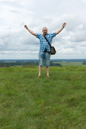 conquest: the man in a checkered shirt rejoices to conquest of the hill