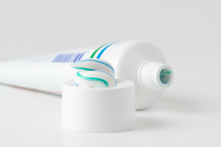 halitosis: toothpaste tube with a small amount of toothpaste on the cap Stock Photo