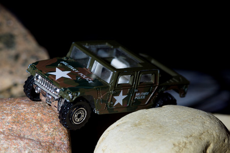 sneaks: small military vehicle sneaks between the huge stones Stock Photo