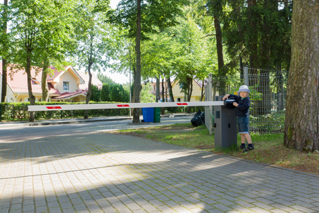 ownership and control: the little boy operates a barrier and blocks the road