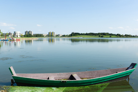 landscape mode: the old wooden boat on the lake with a beautiful view of the city