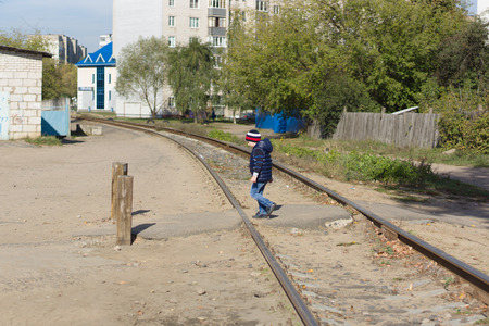 transfers: the boy transfers the railway tracks located in the city Stock Photo