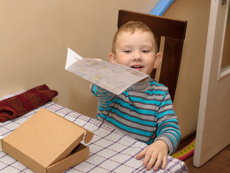 cardboard only: boy sitting at a table with a cardboard box in which lies a wooden constructor
