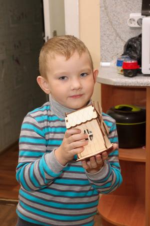 striped vest: boy in a striped vest assembled wooden toy windmill Stock Photo