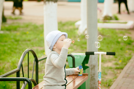fashionable boy blowing bubbles in a city park Stock Photo