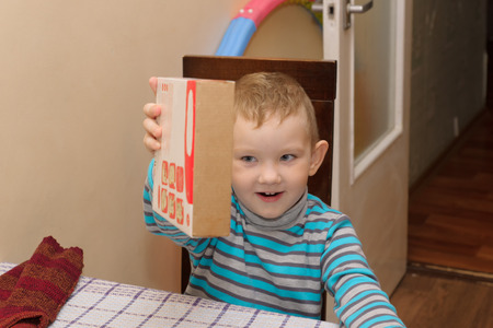 constructor: boy sitting at a table with a cardboard box in which lies a wooden constructor