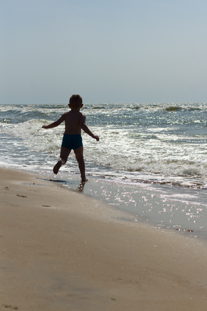 swimming trunks: the little boy in blue swimming trunks has a good time at the sea
