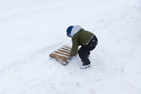 boy with sleds are made of planks on the snow in winter