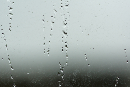 watered: Water droplets and water streams on glass Stock Photo