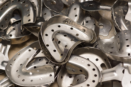 many chrome metal dental impression tray of various sizes Stock Photo