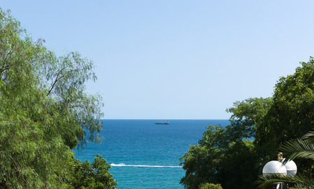 the blue sea surface with small ships on the horizon Imagens