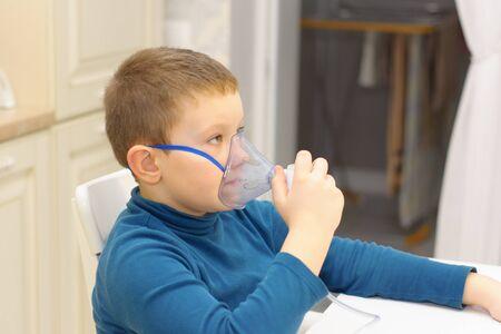 the boy treats a cold with an inhaler 版權商用圖片