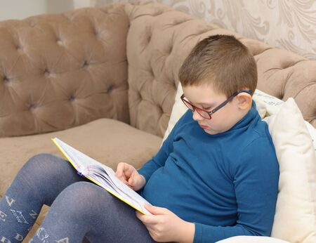 boy in glasses reading a thick book while sitting on the couch