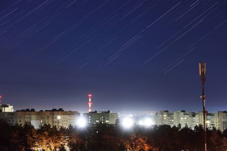 shooting stars shine in the night sky above the city