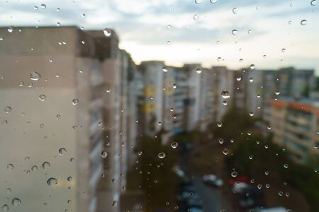 An amazing photography of some waterdrops over the window after summer rain in the city