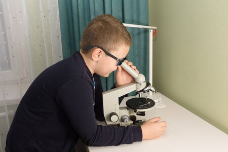 boy in glasses and a jacket sits at a table and does a school task Banque d'images