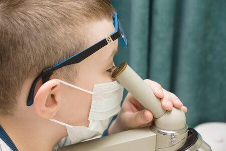 boy in a protective mask with a microscope is looking for a cure for the virus