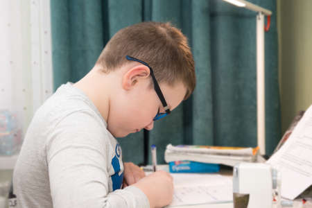 little boy sits at a table and does school lessons