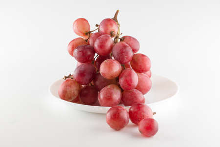 bunch of fresh grapes lies on a dinner plate on a white background Stock Photo