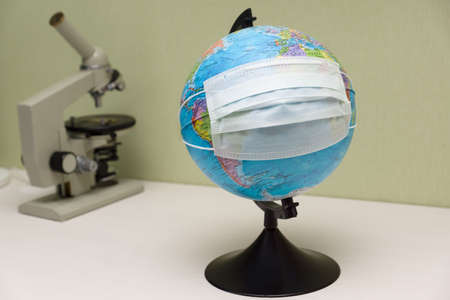 microscope and a globe with a protective mask stand on the table and symbolize the fight Stock Photo