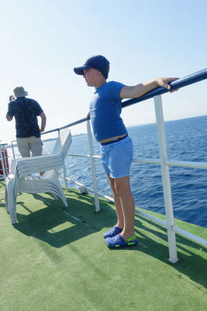 boy on a ship sets sail in the blue sea