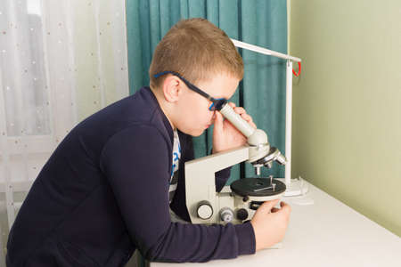boy in glasses and a jacket sits at a table and does a school task Stock Photo