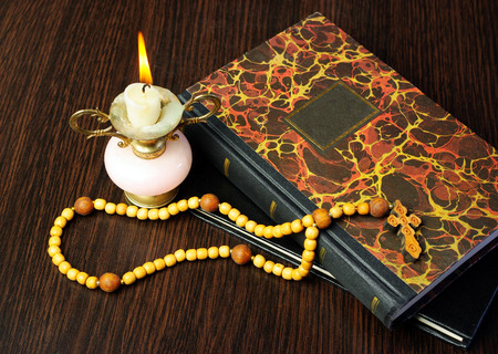 Christian cross on bible and burning candle Stock Photo