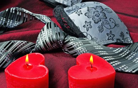 Close-up photo of gray men's tie and women's bra. Prelude of love. Romantic evening.