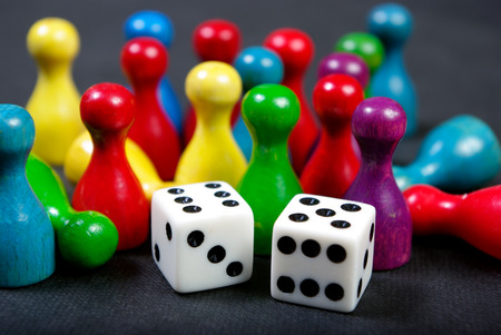 Colorful play figures with dice on board. Close up. Stockfoto