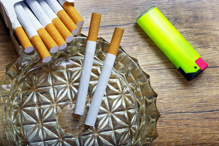 a pack of cigarettes an ashtray and a lighter
