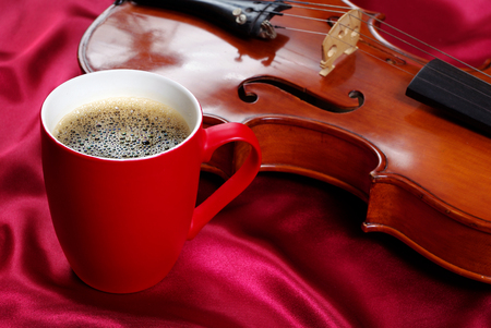 cup of coffee and a violin on a red silk background
