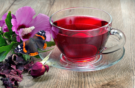 A cup of tea on a wooden table. Hibiscus flower. Vitamin tea for cold and flu