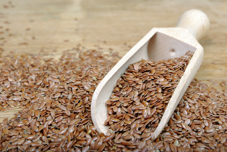 Flax seeds in wooden scoop. close up