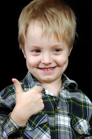 smiling child with thumbs up sign. laughing little boy shows like sign.