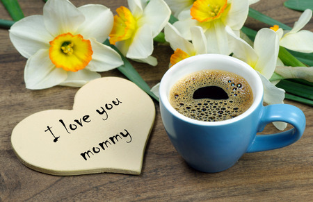 bouquet and a cup of coffee. narcissus and a cup of coffee. coffee and a note i love you. inscription i love you. top view. copy spaces Stockfoto