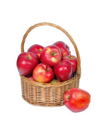 Manzanas rojas en canasta de mimbre aislar en blanco