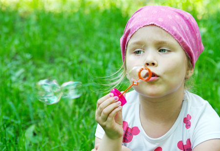 a little girl blowing soap bubbles Reklamní fotografie - 123819954