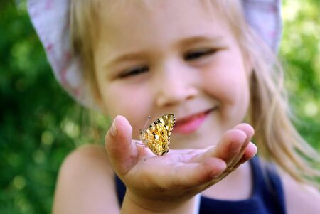Butterfly sitting on the hand of a child. Child with a butterfly. Butterfly painted girl Selective focus.
